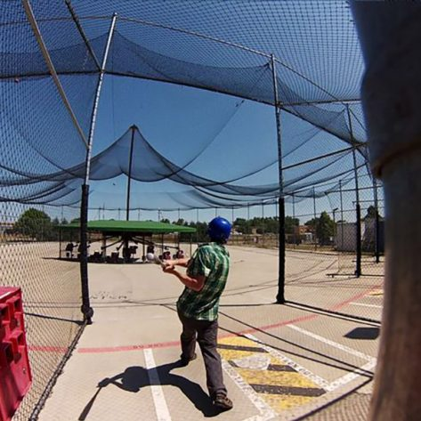 Man hitting a ball in an ABC batting cage