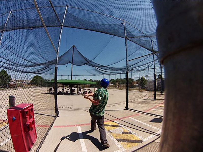 history of batting cages, Man hitting ball in ABC outdoor batting cage