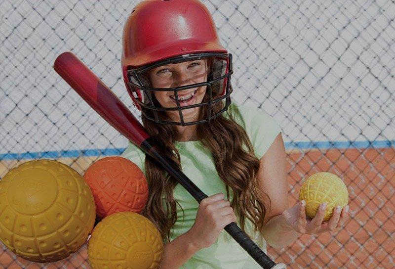 Little girl holding ABC bat and baseball