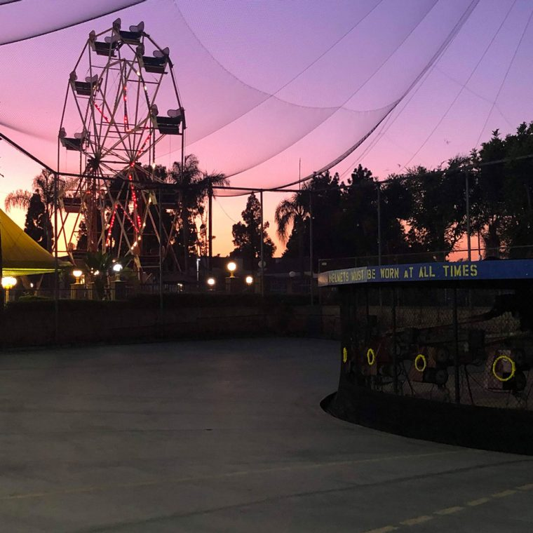 Outdoor batting machine image at sunset with ferris wheel in background