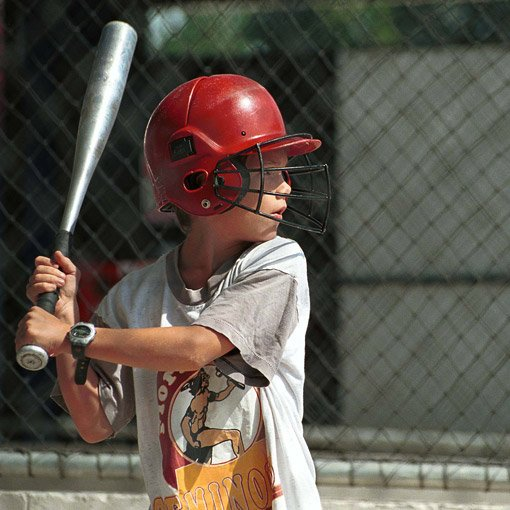 Little boy with face mask helmet holding a bat