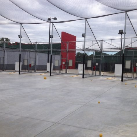 ABC outdoor batting cages and balls on ground